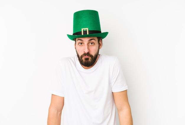 Jonge blanke man met een saint patricks hoed geïsoleerd haalt zijn schouders op en opent verwarde ogen. Premium Foto