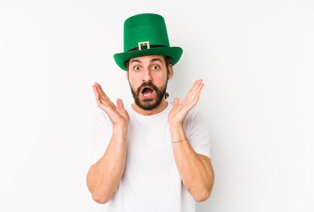 Jonge blanke man met een saint patricks hoed geïsoleerd verrast en geschokt. Premium Foto
