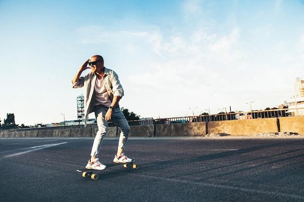 Jonge blanke man rijden op longboard of skateboard, modern schot in filmkorreleffect en vintage stijl. Gratis Foto