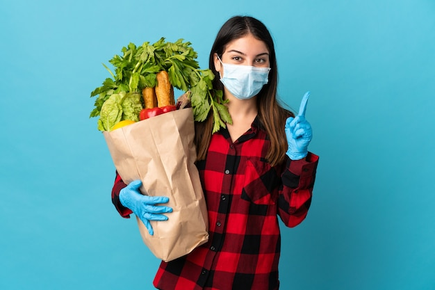 Jonge blanke met groenten en masker geïsoleerd op blauw met een geweldig idee Premium Foto