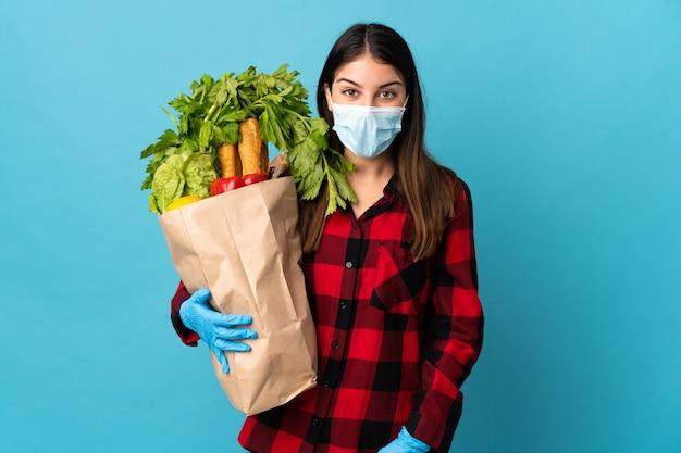 Jonge blanke met groenten en masker geïsoleerd op blauw met verbazing en geschokt gelaatsuitdrukking Premium Foto