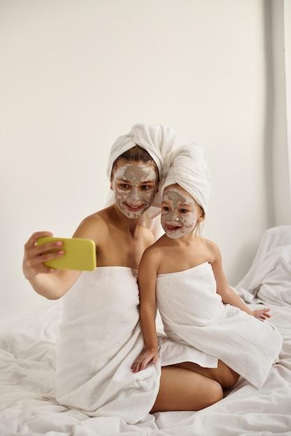 Jonge blanke moeder en dochtertje met ingepakt haar in witte badhanddoeken met een masker op hun gezicht hebben plezier en maken selfies aan de telefoon Premium Foto