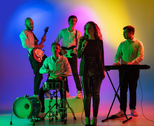 Jonge blanke muzikanten, band optreden, spelen op verloop ruimte in neonlicht. concept van muziek, hobby, festival Gratis Foto