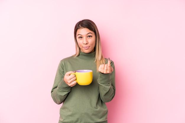 Jonge blanke vrouw die een kopje koffie houdt en met de vinger naar je wijst alsof ze dichterbij komen. Premium Foto