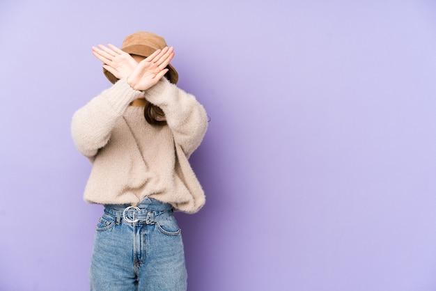 Jonge blanke vrouw geïsoleerd op paarse ruimte twee armen gekruist, ontkenning concept. Premium Foto