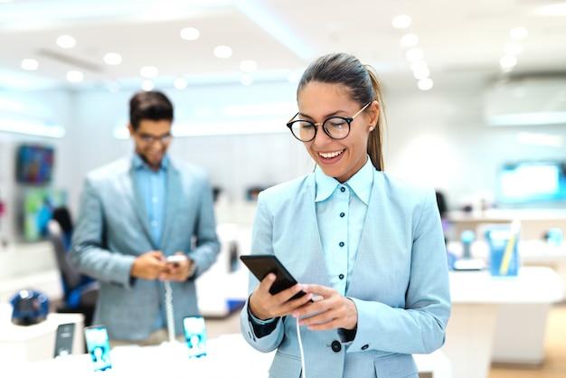 Jonge blanke vrouw gekleed in pak uitproberen van nieuwe slimme telefoon. tech store interieur. Premium Foto