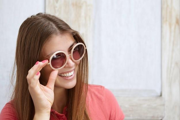 Jonge blanke vrouw met lang blond haar en roze nagels glimlachen terwijl ze haar stijlvolle ronde tinten aanpast. vrolijke vrouw met plezier binnenshuis proberen op zonnebril. Gratis Foto