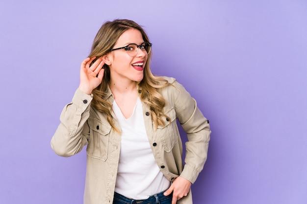 Jonge blanke vrouw probeert een roddel te luisteren. Premium Foto