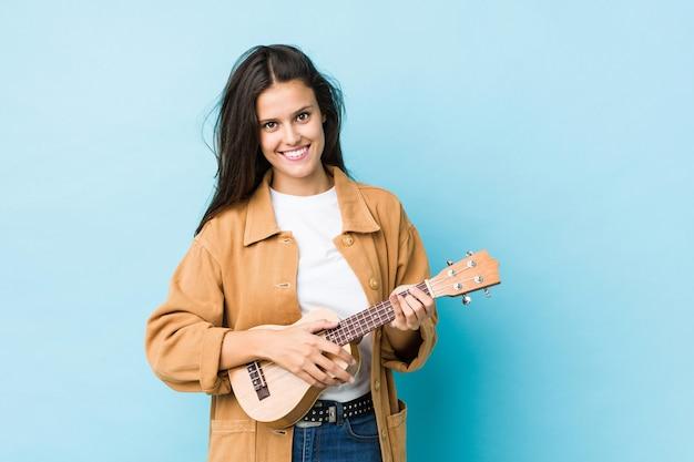 Jonge blanke vrouw spelen ukelele geïsoleerd op blauw Premium Foto