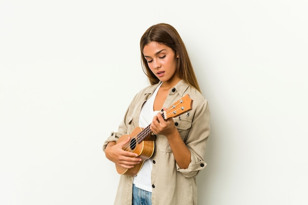Jonge blanke vrouw spelen ukelele geïsoleerd Premium Foto
