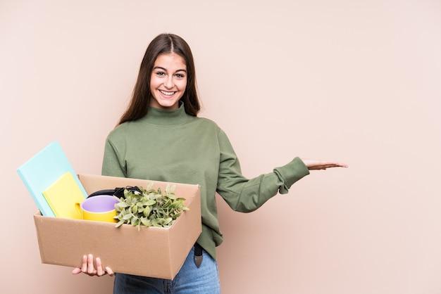 Jonge blanke vrouw verhuizen naar een nieuw huis geïsoleerd met een kopie ruimte op een palm en een andere hand op de taille te houden. Premium Foto