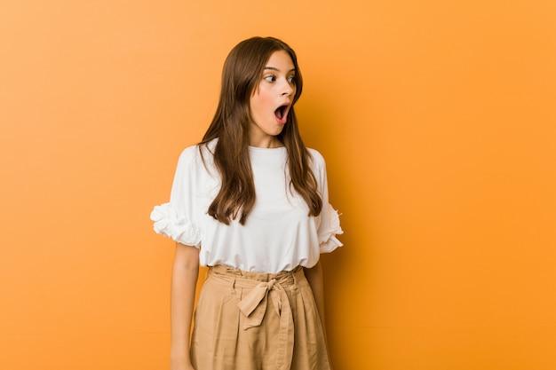 Jonge blanke vrouw wordt geschokt omdat ze iets heeft gezien. Premium Foto