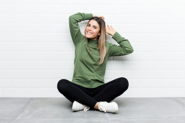 Jonge blanke vrouw zittend op de vloer strekken armen, ontspannen positie. Premium Foto