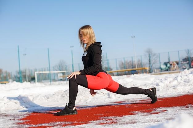 Jonge blanke vrouwelijke blonde in violet beenkappen uitrekkende oefening Premium Foto