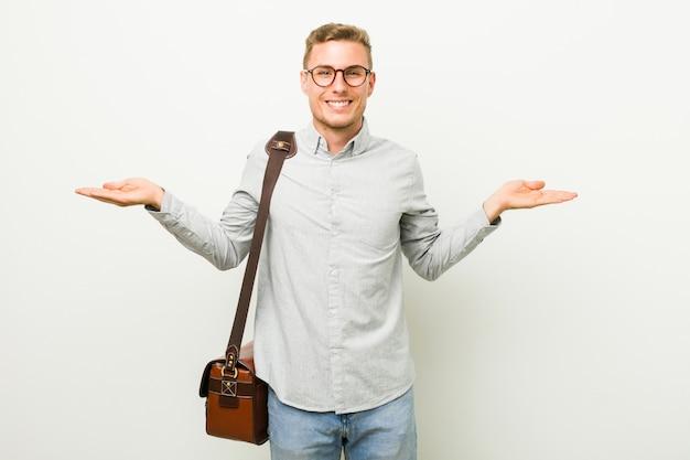 Jonge blanke zakenman maakt schaal met armen, voelt zich gelukkig en zelfverzekerd. Premium Foto