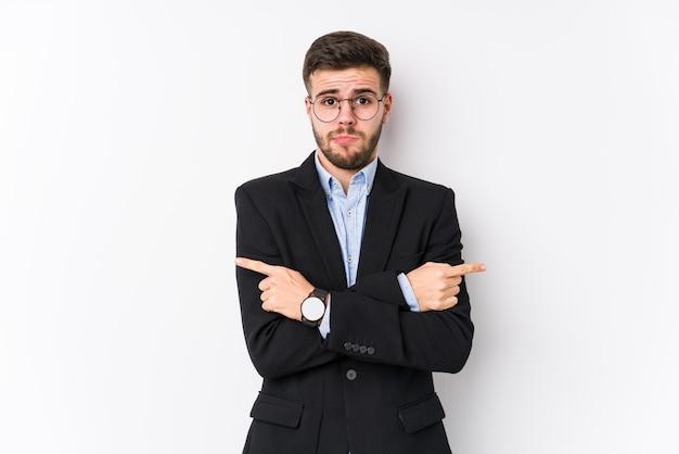 Jonge blanke zakenman poseren in een witte muur geïsoleerd jonge blanke zakenman wijst zijwaarts, probeert te kiezen tussen twee opties. Premium Foto