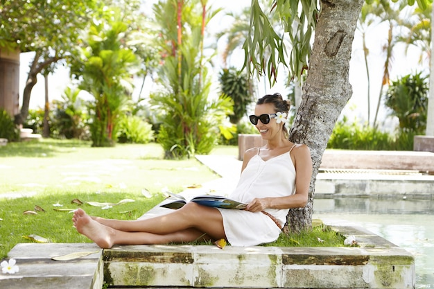 Jonge blanke zwangere vrouw in stijlvolle tinten verbergen van de zon in de schaduw onder de boom, gelukkig lachend tijdens het lezen van een tijdschrift. Gratis Foto