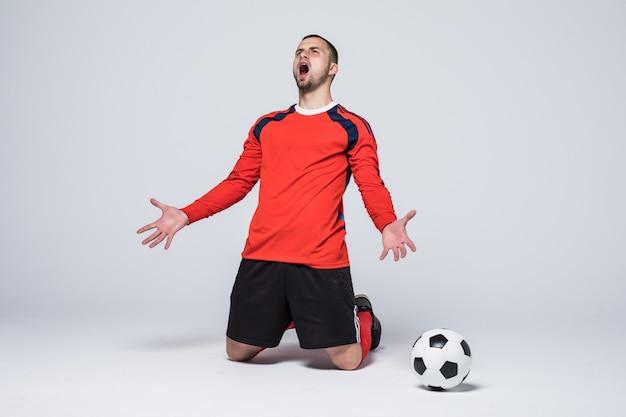 Jonge blij en opgewonden voetballer in rode trui scoren doel vieren Gratis Foto