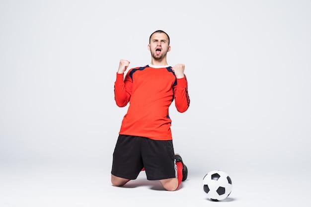 Jonge, blij en opgewonden voetballer in trui scorend doel vieren Gratis Foto