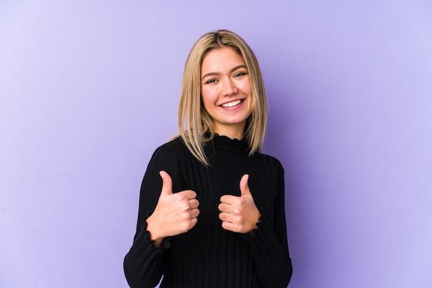 Jonge blonde blanke vrouw die beide duimen opheft, glimlachend en zelfverzekerd. Premium Foto