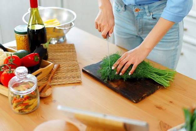 Jonge blonde blanke vrouw snijden groenten voor salade in haar keuken Premium Foto