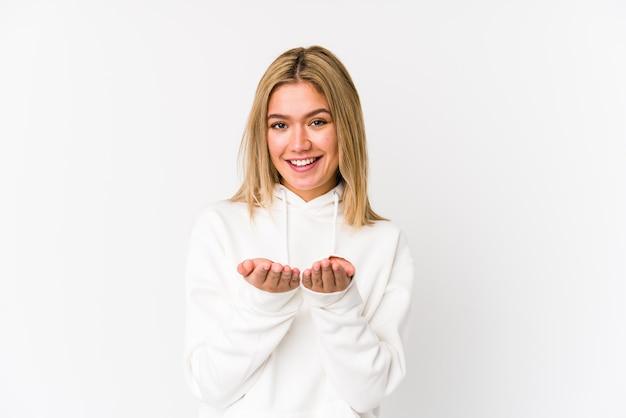 Jonge blonde kaukasische vrouw die iets met palmen houdt, aan camera aanbiedt. Premium Foto