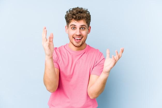 Jonge blonde krullende blanke man die een aangename verrassing ontvangt, opgewonden en handen opheft. Premium Foto
