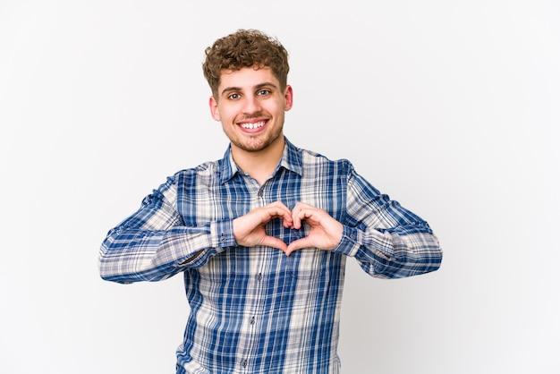 Jonge blonde krullende haar kaukasische mens die en een hartvorm met handen glimlacht toont. Premium Foto