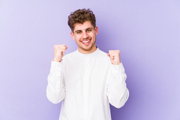 Jonge blonde krullende haarmens die een overwinning, een hartstocht en een enthousiasme, gelukkige uitdrukking vieren Premium Foto