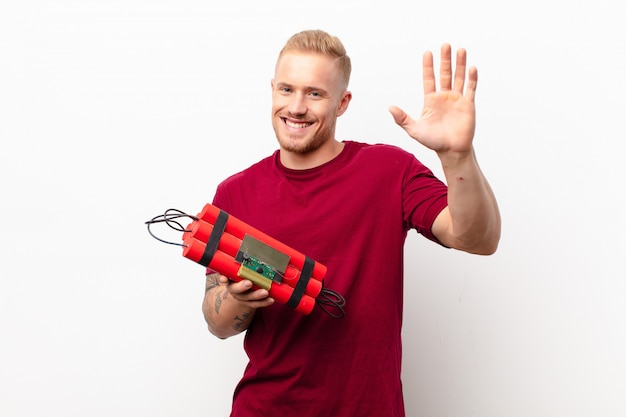 Jonge blonde man die vrolijk en opgewekt glimlacht, hand zwaait, je verwelkomt en begroet, of afscheid neemt tegen een witte muur met een dynamietexplosief Premium Foto