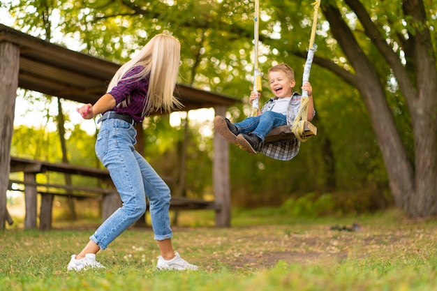 Jonge blonde moeder schudt haar zoontje op een schommel in een groen park. gelukkige jeugd. Premium Foto