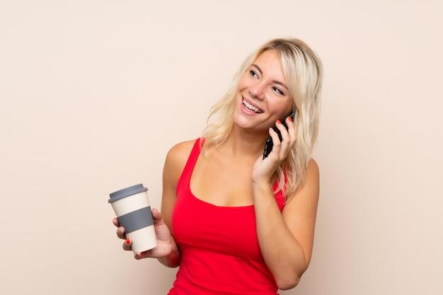 Jonge blonde te houden koffie van de vrouwenholding en mobiel Premium Foto