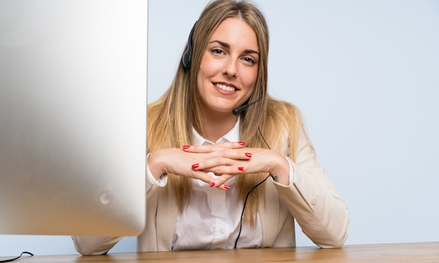 Jonge blonde telemarketer vrouw en het glimlachen Premium Foto