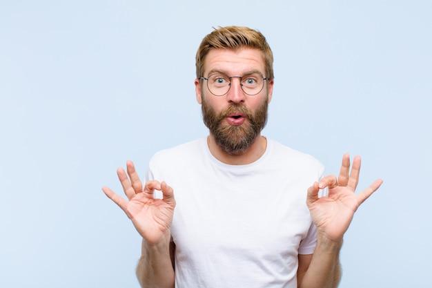 Jonge blonde volwassen man die zich geschokt, verbaasd en verrast voelt, goedkeuring toont die goed teken met beide handen maakt Premium Foto