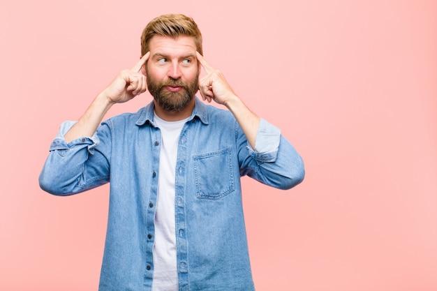 Jonge blonde volwassen man verward of twijfelen, zich te concentreren op een idee Premium Foto