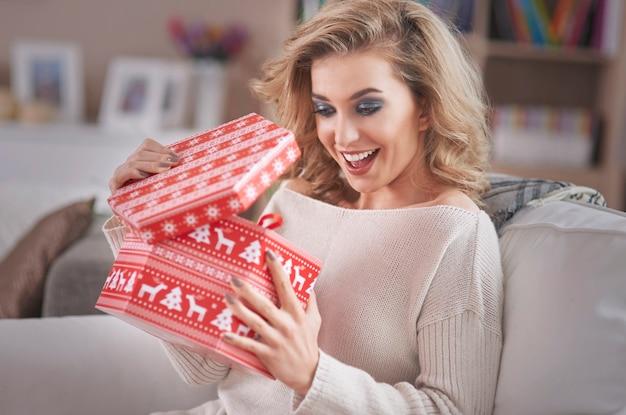 Jonge blonde vrouw die een gift van kerstmis opent Gratis Foto