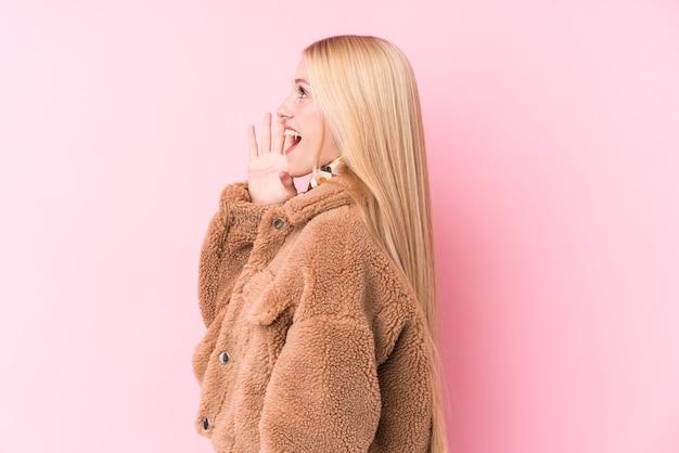 Jonge blonde vrouw die een jas draagt tegen een roze muur die en palm dichtbij geopende mond houdt houdt. Premium Foto