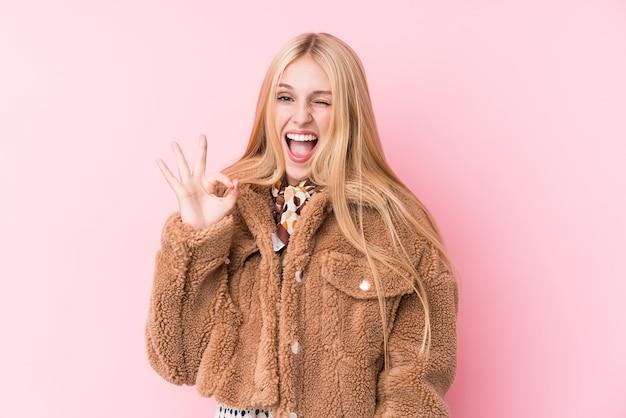Jonge blonde vrouw die een jas draagt tegen een roze muur, knipoogt en houdt een goed gebaar met de hand. Premium Foto