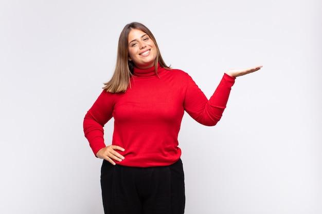 Jonge blonde vrouw die lacht, zich zelfverzekerd, succesvol en gelukkig voelt, concept of idee toont op kopie ruimte aan de zijkant Premium Foto