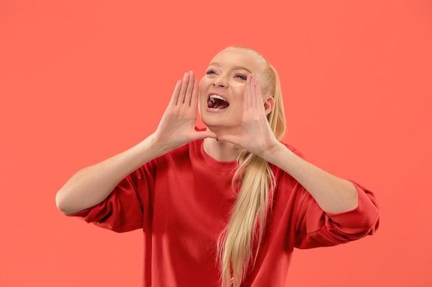 Jonge blonde vrouw die op koraalachtergrond gilt Gratis Foto