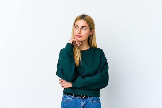 Jonge blonde vrouw die opzij kijkt met een twijfelachtige en sceptische uitdrukking. Premium Foto