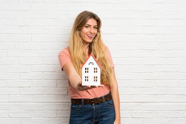 Jonge blonde vrouw die over witte bakstenen muur een klein huis houdt Premium Foto