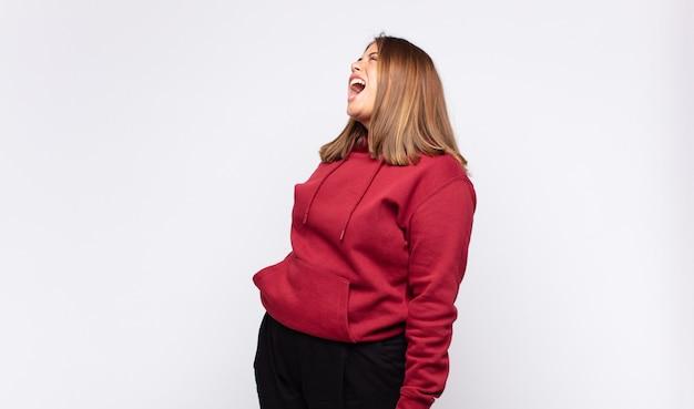Jonge blonde vrouw die woedend schreeuwt, agressief schreeuwt, gestrest en boos kijkt Premium Foto