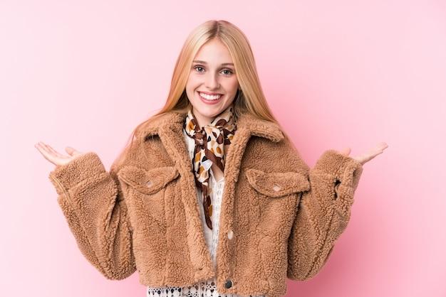 Jonge blonde vrouw draagt een jas tegen een roze muur maakt schaal met armen, voelt zich gelukkig en zelfverzekerd. Premium Foto