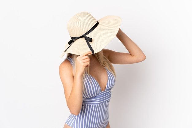 Jonge blonde vrouw geïsoleerd op een witte achtergrond in zwembroek in zomervakantie Premium Foto