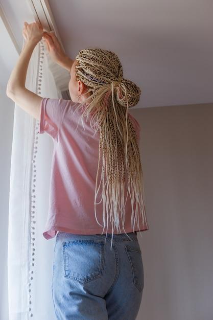 Jonge blonde vrouw gordijnen ophangen bij het raam Premium Foto