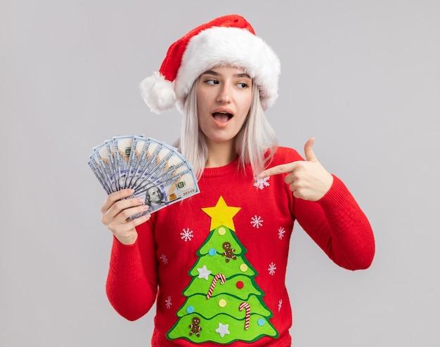 Jonge blonde vrouw in kerstmissweater en santahoed die contant geld houden dat met wijsvinger naar blij en verrast geld richt Gratis Foto