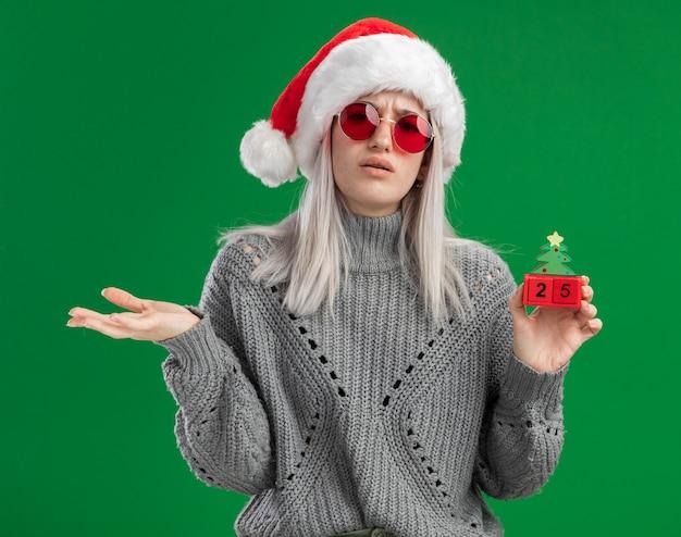 Jonge blonde vrouw in winter trui en kerstmuts draagt ?? een rode bril met speelgoed blokjes met kerstdatum op zoek verward met arm uit staande over groene achtergrond Gratis Foto