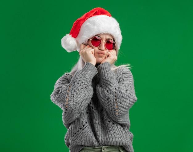 Jonge blonde vrouw in winter trui en kerstmuts dragen rode bril kijken camera maken grimas plezier staande over groene achtergrond Gratis Foto