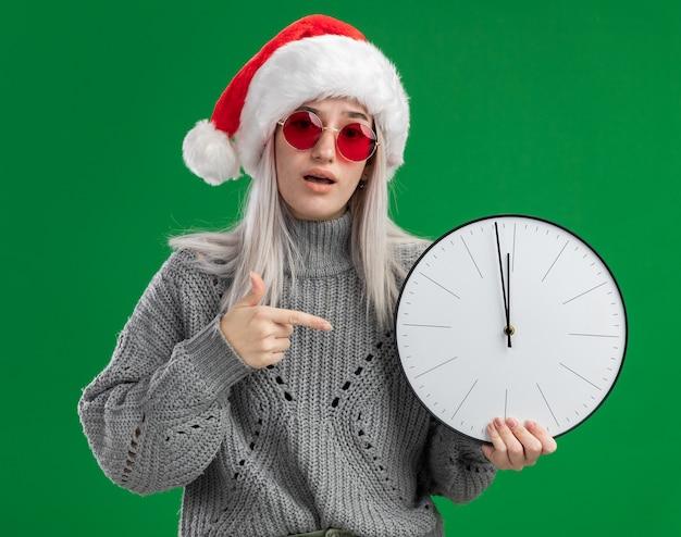 Jonge blonde vrouw in winter trui en kerstmuts met rode bril houden wandklok wijzend met wijsvinger naar het kijken verward staande op groene achtergrond Gratis Foto